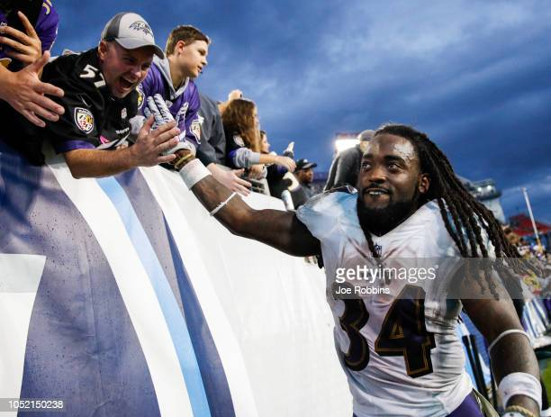 Alex Collins of the Baltimore Ravens high fives fans after beating the Tennessee Titans at Nissan Stadium on October 14 2018 in Nashville Tennessee