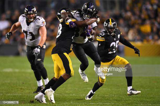 Alex Collins of the Baltimore Ravens is wrapped up for a tackle by Vince Williams of the Pittsburgh Steelers in the second half during the game at...