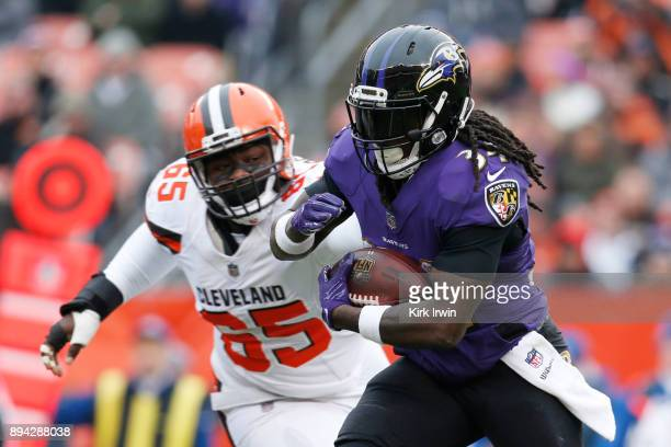 Alex Collins of the Baltimore Ravens runs the ball by Larry Ogunjobi of the Cleveland Browns in the first half at FirstEnergy Stadium on December 17...
