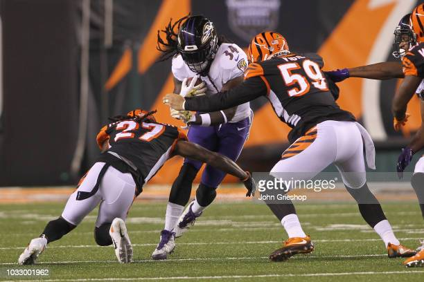 Alex Collins of the Baltimore Ravens runs the football upfield against Dre Kirkpatrick and Nick Vigil of the Cincinnati Bengals during their game at...