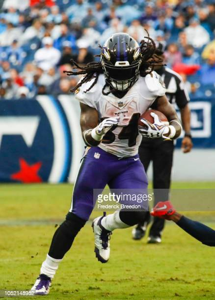 Alex Collins of the Baltimore Ravens runs with the ball against the Tennessee Titans during the third quarter at Nissan Stadium on October 14 2018 in...