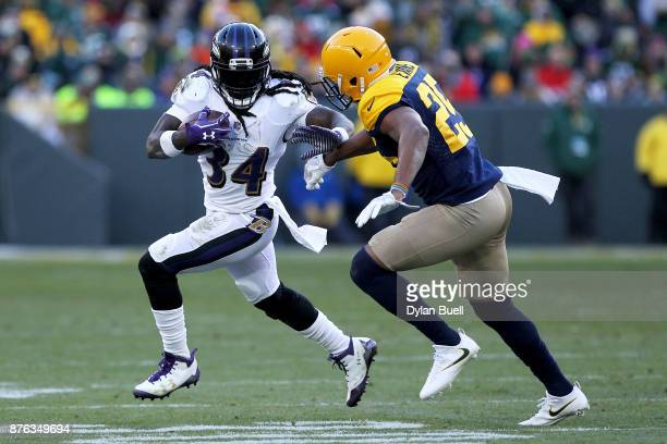 Alex Collins of the Baltimore Ravens runs with the ball while being chased by Marwin Evans of the Green Bay Packers in the fourth quarter at Lambeau...
