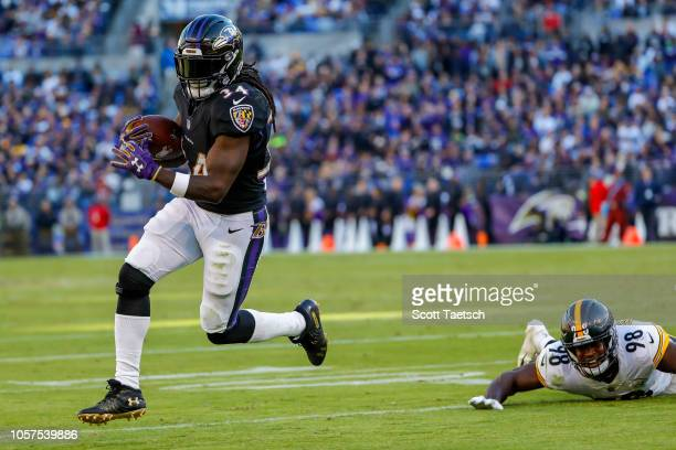Alex Collins of the Baltimore Ravens rushes past Vince Williams of the Pittsburgh Steelers for a touchdown during the third quarter at MT Bank...