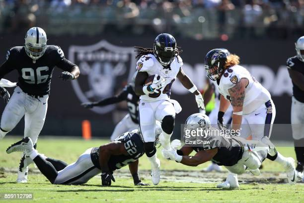 Alex Collins of the Baltimore Ravens rushes with the ball against the Oakland Raiders during their NFL game at OaklandAlameda County Coliseum on...