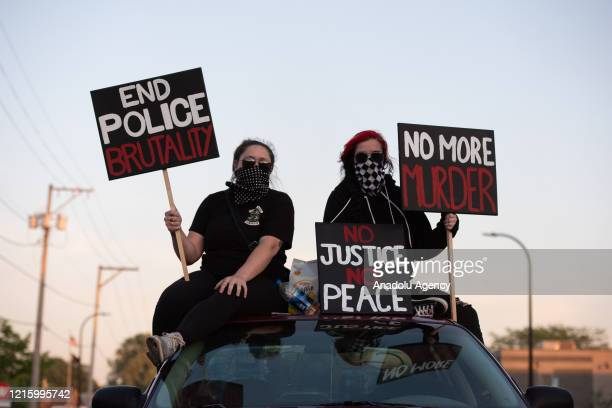 Alex Conway left and Bekka Koch hold signs outside the Minneapolis 3rd police precinct on Thursday May 28 during the third day of protests over the...