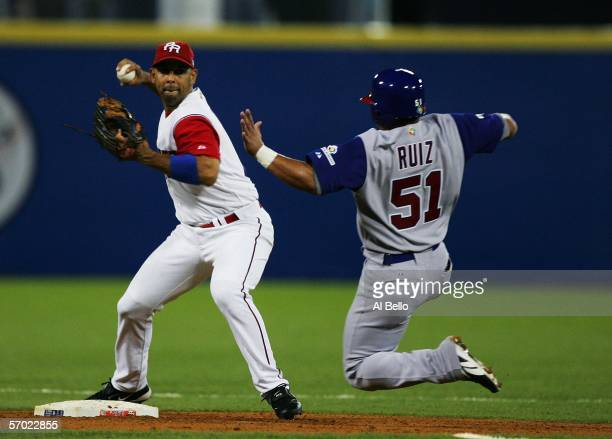 Alex Cora of Puerto Rico turns a double play as Carlos Ruiz of Panama is out at second base during their game at the World Baseball Classic at Hiram...