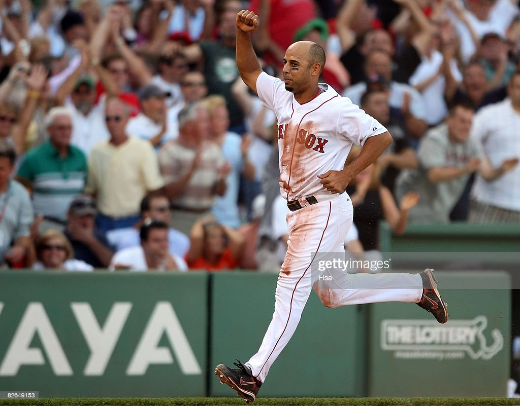 Alex Cora #13 of the Boston Red Sox celebrates as he scores the game winning run in the ninth inninng against the Baltimore Orioles on September 3, 2008 at Fenway Park in Boston, Massachusetts. The Boston Red Sox defeated the Baltimore Orioles 5-4.