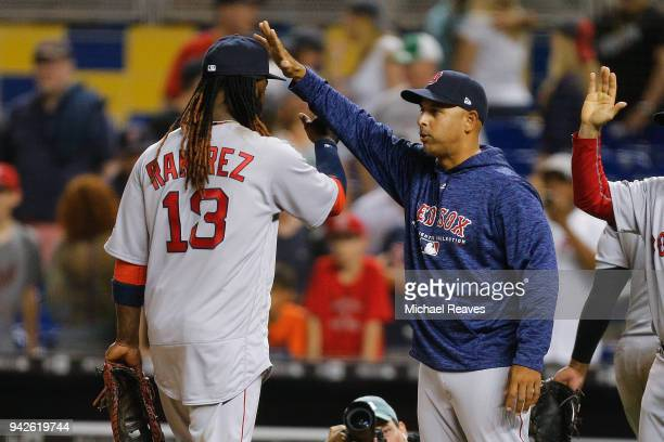Alex Cora of the Boston Red Sox celebrates with Hanley Ramirez after they defeated the Miami Marlins in 13 innings at Marlins Park on April 3 2018 in...