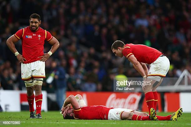Alex Cuthbert of Wales lies dejected on the pitch as George North of Wales stands over him with Taulupe Faletau of Wales looking on during the 2015...