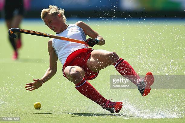 Alex Danson of England falls as she runs with the ball during the Women's preliminary match between England and Wales at Glasgow National Hockey...