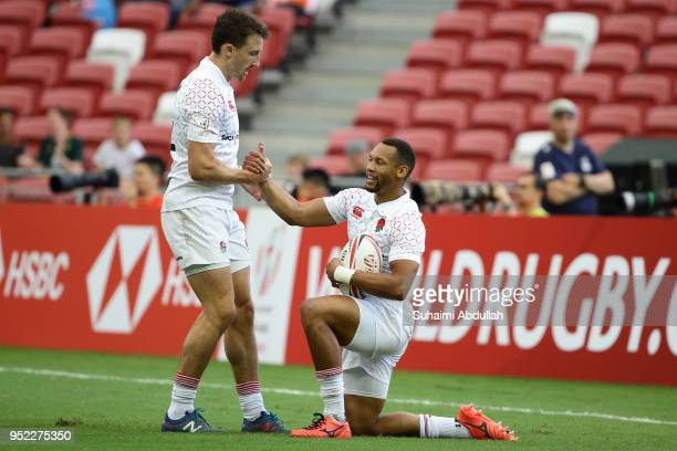 Alex Davis congratulates Dan Norton of England after he scores a try during the 2018 Singapore Sevens Pool B match between Kenya and England at...