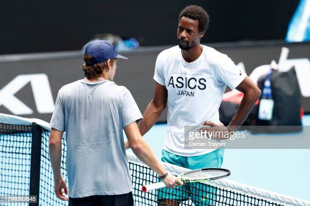 Alex de Minaur of Australia and Gael Monfils of France speak at the net during a practice session at Melbourne Park on January 30, 2021 in Melbourne,...
