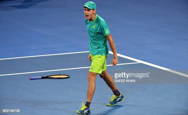 TOPSHOT Alex De Minaur of Australia celebrates his victory against Milos Raonic of Canada in their men's singles second round match at Pat Rafter...