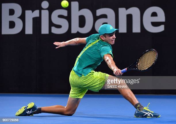 TOPSHOT Alex De Minaur of Australia hits a return against Milos Raonic of Canada during their men's singles second round match at Pat Rafter Arena...