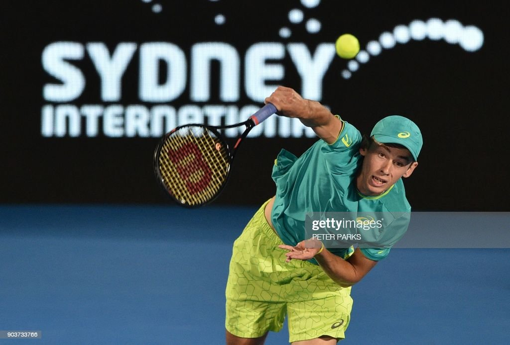 Alex De Minaur of Australia hits a serve to Feliciano López of Spain in their men's singles quarter-final match at the Sydney International tennis tournament in Sydney on January 11, 2018. /