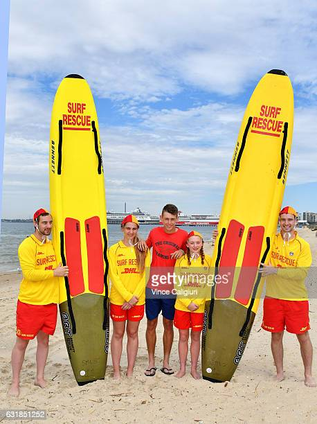 Alex De Minaur of Australia poses with members of the Sth Melbourne Life Saving club during day two of the 2017 Australian Open at Melbourne Park on...