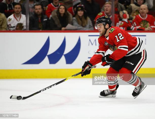 Alex DeBrincat of the Chicago Blackhawks advances the puck against the Calgary Flames at the United Center on December 02 2018 in Chicago Illinois...