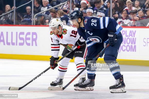 Alex DeBrincat of the Chicago Blackhawks and Blake Wheeler of the Winnipeg Jets get set during a first period faceoff at the Bell MTS Place on...