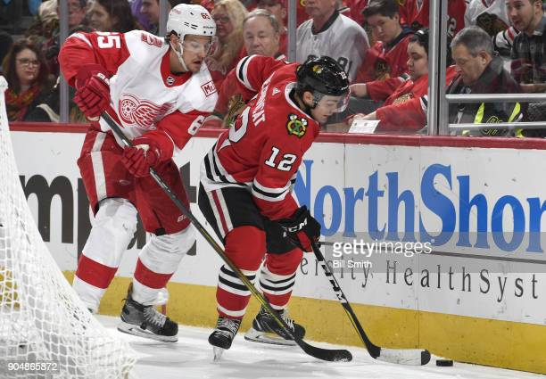 Alex DeBrincat of the Chicago Blackhawks and Danny DeKeyser of the Detroit Red Wings approach the puck in the first period at the United Center on...