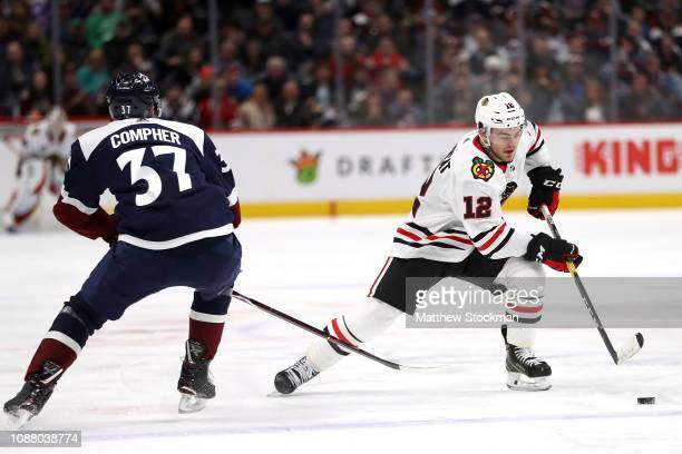 Alex DeBrincat of the Chicago Blackhawks brings the puckj down the ice against JT Compher of the Colorado Avalanche in the third period at the Pepsi...
