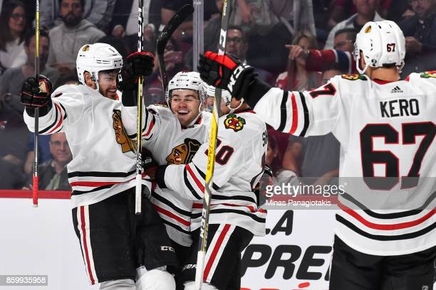 Alex DeBrincat of the Chicago Blackhawks celebrates his first period goal with teammates against the Montreal Canadiens during the NHL game at the...