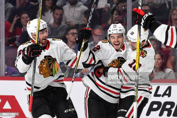 Alex DeBrincat of the Chicago Blackhawks celebrates his first period goal with teammates Michal Kempny and Patrick Sharp of the Chicago Blackhawks...