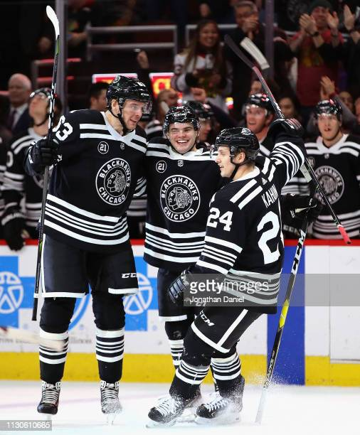 Alex DeBrincat of the Chicago Blackhawks celebrates his hat trick with teammates Carl Dahlstrom and Dominik Kahun against the Ottawa Senators at the...
