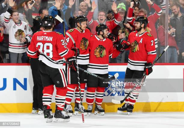 Alex DeBrincat of the Chicago Blackhawks celebrates with Richard Panik and Brent Seabrook after scoring against the New York Rangers in the second...