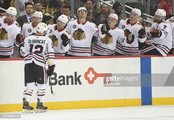Alex DeBrincat of the Chicago Blackhawks celebrates with teammates on the bench after scoring a goal in the first period during the game against the...