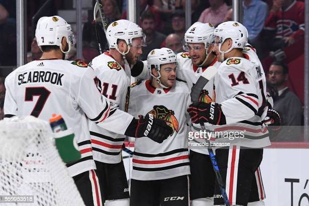 Alex DeBrincat of the Chicago Blackhawks celebrates with teammates after scoring a goal against the Montreal Canadiens in the NHL game at the Bell...