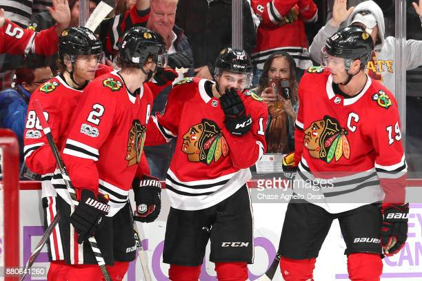 Alex DeBrincat of the Chicago Blackhawks celebrates with teammates after scoring a hattrick in the second period against the Anaheim Ducks at the...