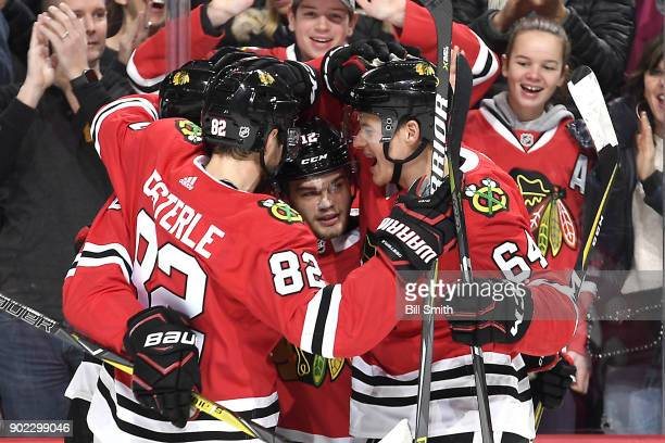 Alex DeBrincat of the Chicago Blackhawks celebrates with teammates including David Kampf after scoring against the Edmonton Oilers in the first...
