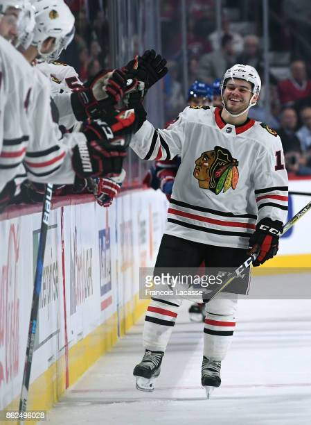 Alex DeBrincat of the Chicago Blackhawks celebrates with the bench after scoring a goal against the Montreal Canadiens in the NHL game at the Bell...