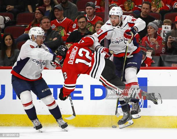 Alex DeBrincat of the Chicago Blackhawks collides with Tom Wilson and Dmitry Orlov of the Washington Capitals at the United Center on February 17...