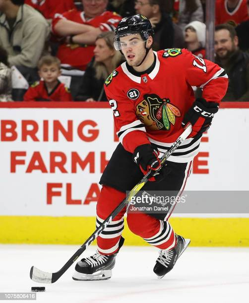 Alex DeBrincat of the Chicago Blackhawks controls the puck against the Minnesota Wild at the United Center on December 27 2018 in Chicago Illinois...