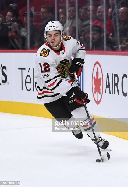 Alex DeBrincat of the Chicago Blackhawks controls the puck against the Montreal Canadiens in the NHL game at the Bell Centre on October 10 2017 in...