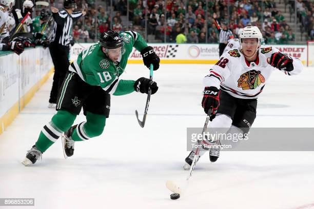 Alex DeBrincat of the Chicago Blackhawks controls the puck against Tyler Pitlick of the Dallas Stars in the first period at American Airlines Center...