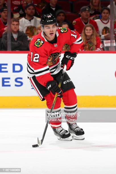 Alex DeBrincat of the Chicago Blackhawks controls the puck in the first period against the Winnipeg Jets at the United Center on October 12 2019 in...