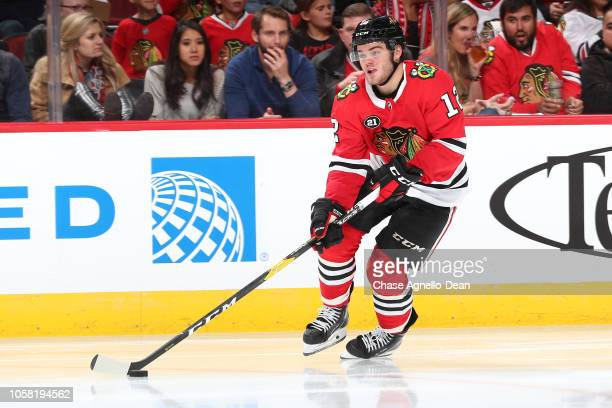 Alex DeBrincat of the Chicago Blackhawks grabs the puck against the St Louis Blues at the United Center on October 13 2018 in Chicago Illinois The...