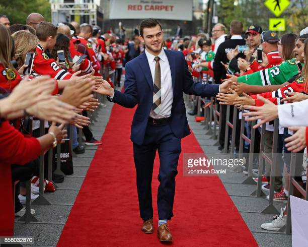 Alex DeBrincat of the Chicago Blackhawks greets fans during a 'red carpet' event before the season opening game against the Pittsburgh Penguins at...