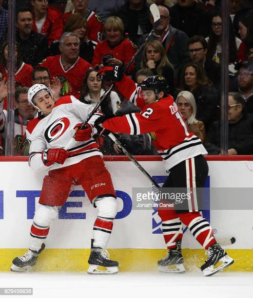 Alex DeBrincat of the Chicago Blackhawks hits Teuvo Teravainen of the Carolina Hurricanes at the United Center on March 8 2018 in Chicago Illinois