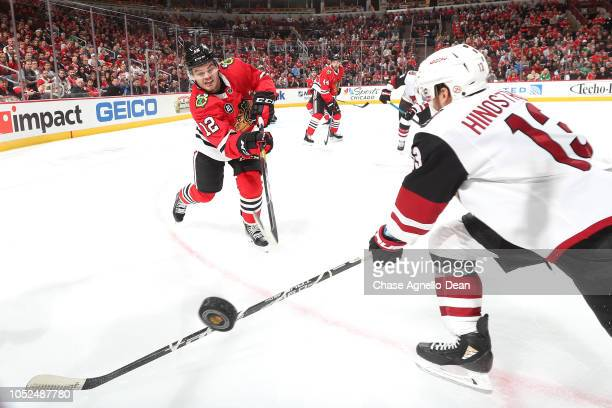 Alex DeBrincat of the Chicago Blackhawks hits the puck past Vinnie Hinostroza of the Arizona Coyotes in the third period at the United Center on...