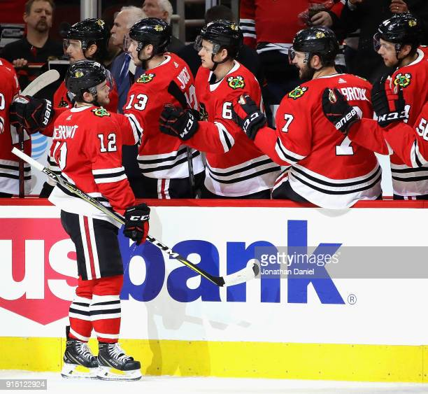 Alex DeBrincat of the Chicago Blackhawks is congratulated by teammates after scoring a first period goal against the Calgary Flames at the United...