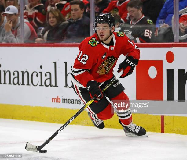 Alex DeBrincat of the Chicago Blackhawks looks to pass against the Vegas Golden Knights at the United Center on November 27 2018 in Chicago Illinois