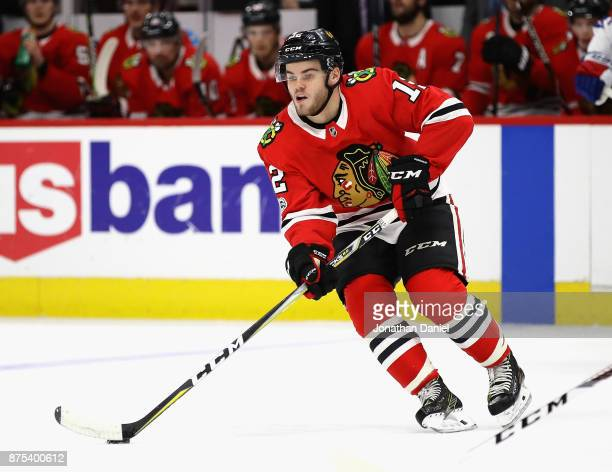 Alex DeBrincat of the Chicago Blackhawks looks to pass against the New York Rangers at the United Center on November 15 2017 in Chicago Illinois The...