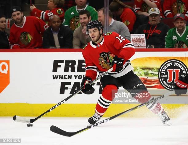Alex DeBrincat of the Chicago Blackhawks looks to pass against the Ottawa Senators at the United Center on February 21 2018 in Chicago Illinois The...