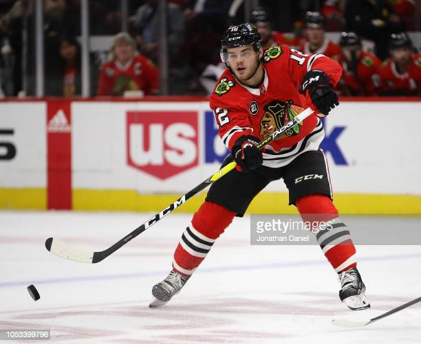 Alex DeBrincat of the Chicago Blackhawks passes against the Arizona Coyotes at the United Center on October18 2018 in Chicago Illinois The Coyotes...