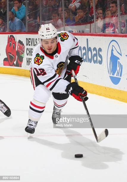 Alex DeBrincat of the Chicago Blackhawks plays the puck against the New Jersey Devils at Prudential Center on December 23 2017 in Newark New Jersey