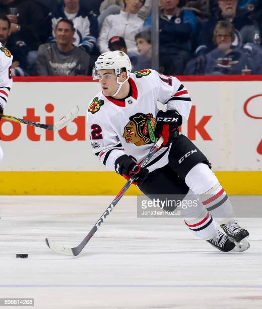 Alex DeBrincat of the Chicago Blackhawks plays the puck down the ice during third period action against the Winnipeg Jets at the Bell MTS Place on...