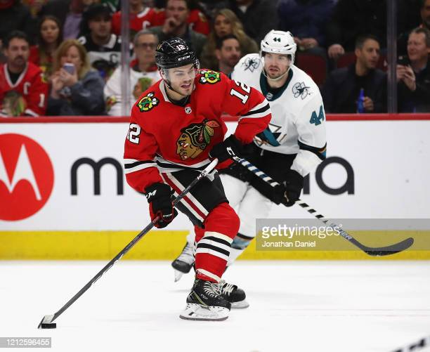 Alex DeBrincat of the Chicago Blackhawks readies to shot next to MarcEdouard Vlasic of the San Jose Sharks at the United Center on March 11 2020 in...